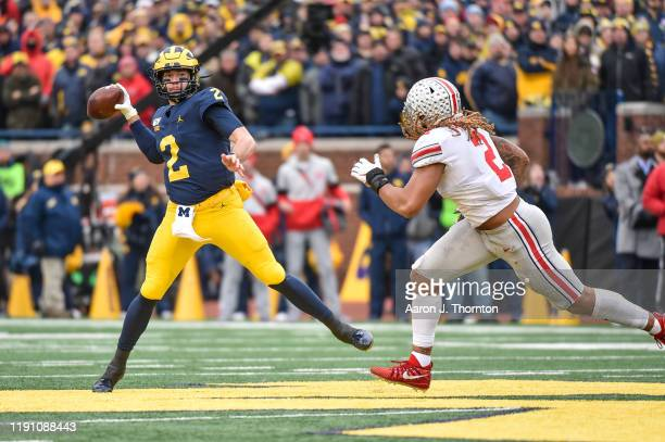 Shea Patterson of the Michigan Wolverines throws a pass while Chase Young of the Ohio State Buckeyes defends during the first half of a college...