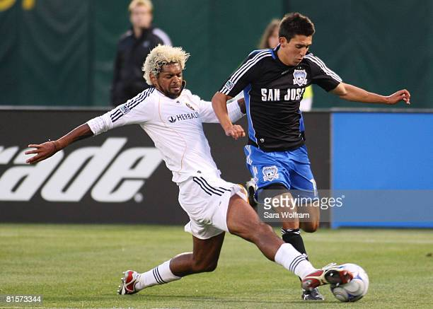 Shea Salinas of the San Jose Earthquakes controls the ball against Abel Xavier of the Los Angeles Galaxy during the MLS game at McAfee Coliseum June...