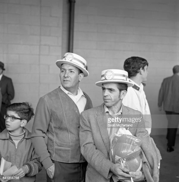 2 middle aged men wearing retro NY Mets hats stand with a young boy and watch Game 5 of the World Series from the walkway around the inside of Shea