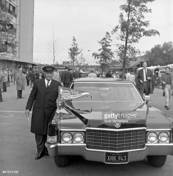 A Limousine driver poses for a photo with his 'Mets Champions' banner proudly displayed on the front of his vehicle after the Mets win it all in Game...