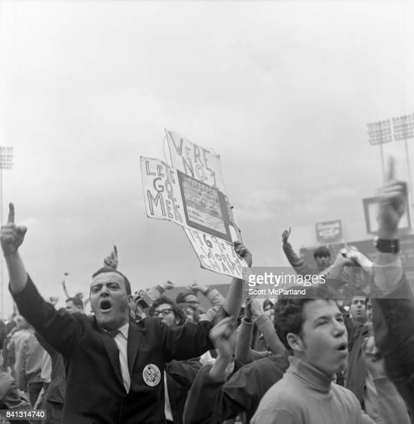 A man holds a victory sign up proclaiming the NY Mets being as other fans storm the field after the Mets win it all in Game 5 of the 1969 World...