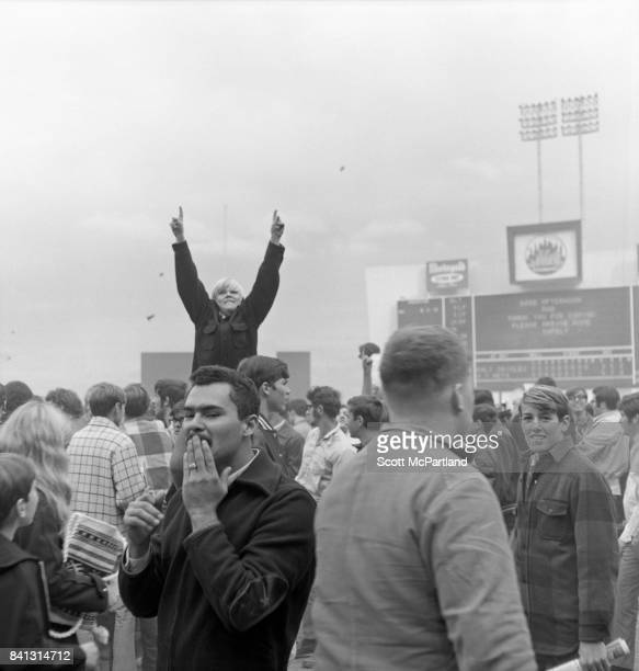 Dirt and grass can be seen being thrown into the air and a young boy throws his arms up in victory as fans storm the field at Shea after the NY Mets...