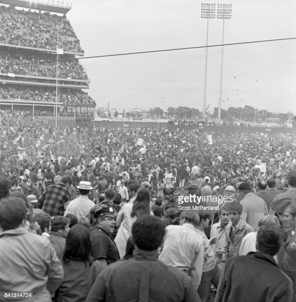 Fan appreciation spirals out of control and dirt clods are thrown high into the air as thousands of fans storm the field after the NY Mets win it all...