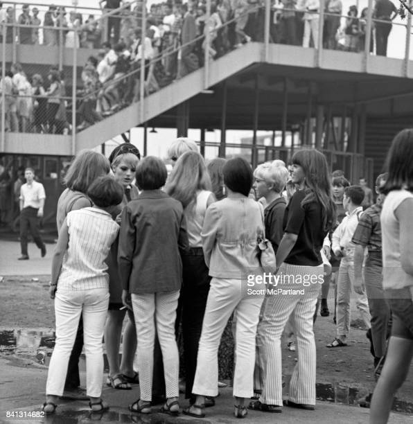 A large group of teenage girls gather in the parking lot of Shea Stadium prior to The Beatles hitting the stage on their last American Tour