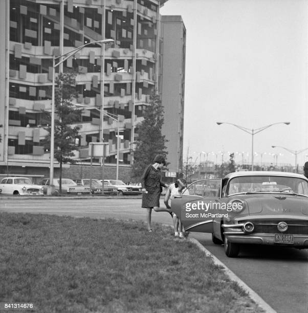 A mother exits a classic Buick with her young daughter in the parking lot of Shea prior to The Beatles taking the stage on their last American Tour