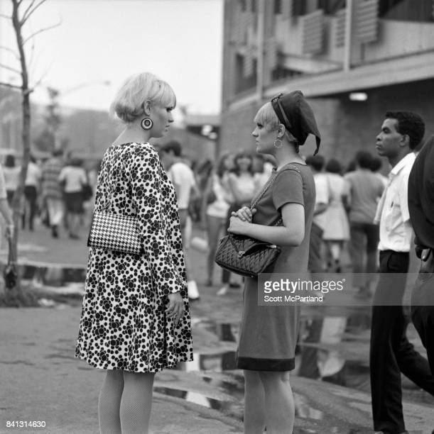 Two teenage girls dressed in classic 60s fashion chat out in front of Shea Stadium before entering to see The Beatles live on their last American Tour