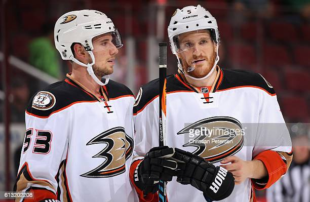 Shea Theodore and Korbinian Holzer of the Anaheim Ducks talk during the preseason NHL game against Arizona Coyotes at Gila River Arena on October 1...