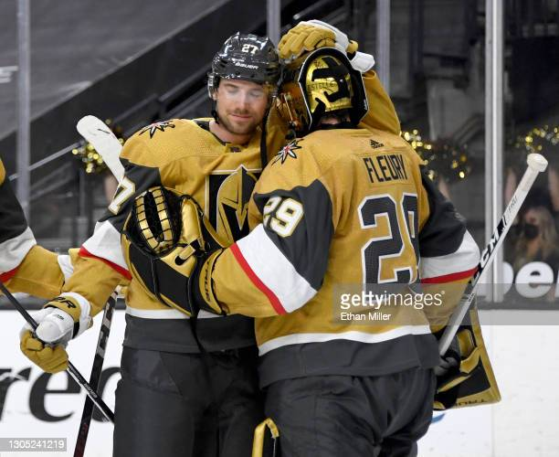 Shea Theodore and Marc-Andre Fleury of the Vegas Golden Knights celebrate on the ice after the team's 5-1 victory over the Minnesota Wild at T-Mobile...