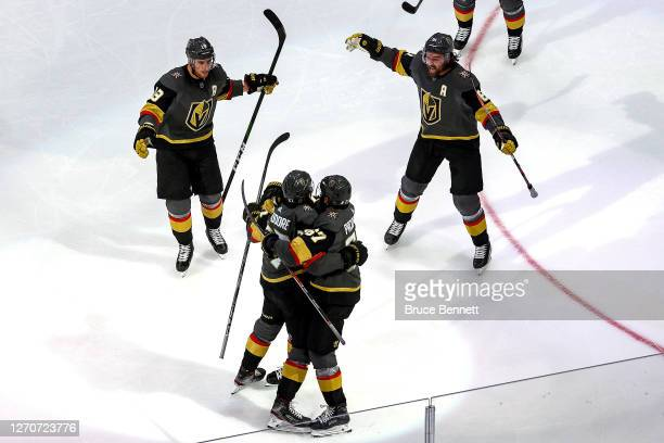 Shea Theodore of the Vegas Golden Knights is congratulated by his teammates after scoring a goal against the Vancouver Canucks1 during the third...