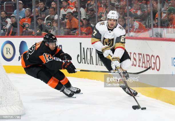 Shea Theodore of the Vegas Golden Knights skates with the puck behind the net while being pursued by Michael Raffl of the Philadelphia Flyers on...