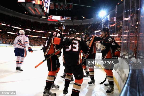 Shea Theodoreand Cam Fowler congratulate Jakob Silfverberg of the Anaheim Ducks after he scored in the third period in Game One of the Western...