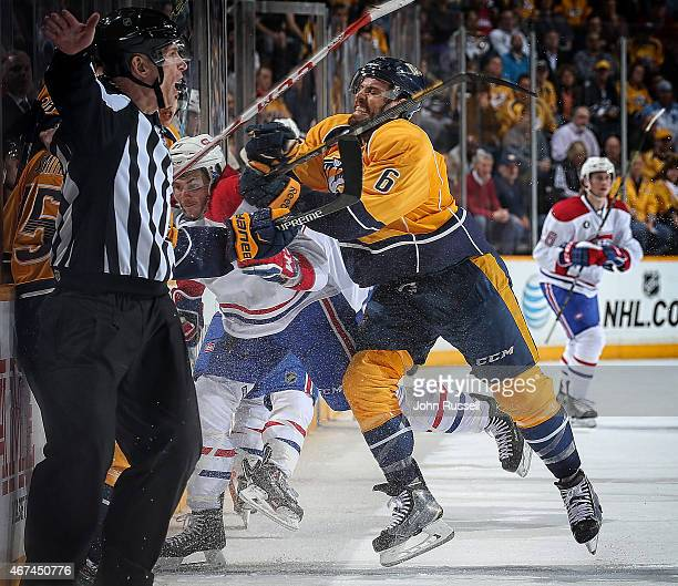 Shea Weber of the Nashville Predators finishes a check against Alex Galchenyuk of the Montreal Canadiens during an NHL game at Bridgestone Arena on...