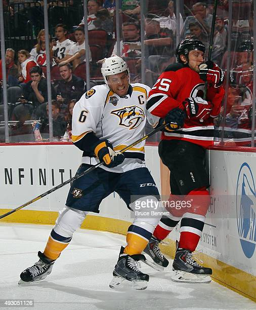 Shea Weber of the Nashville Predators hits Stefan Matteau of the New Jersey Devils into the boards at the Prudential Center on October 13 2015 in...