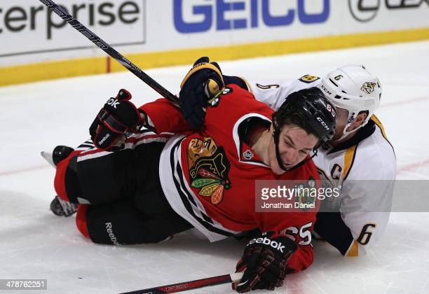 Shea Weber of the Nashville Predators takes down Andrew Shaw of the Chicago Blackhawks at the United Center on March 14 2014 in Chicago Illinois