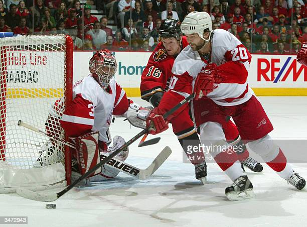Shean Donovan of the Calgary Flames looks for the puck between Robert Lang and Curtis Joseph of the Detroit Red Wings during the second period of...