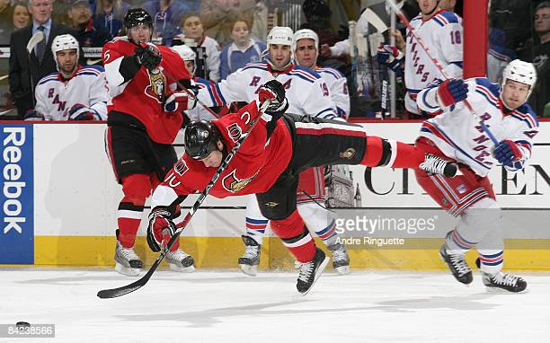 Shean Donovan of the Ottawa Senators is tripped off his feet by Colton Orr of the New York Rangers at Scotiabank Place on January 10, 2009 in Ottawa,...