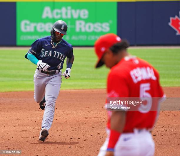 Shed Long Jr. #4 of the Seattle Mariners runs the bases after hitting a two-run home run during the third inning as Santiago Espinal of the Toronto...
