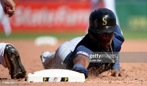 Shed Long of the Seattle Mariners dives back to first base on a pickoff attempt by Joe Musgrove of the Pittsburgh Pirates in the fifth inning during...