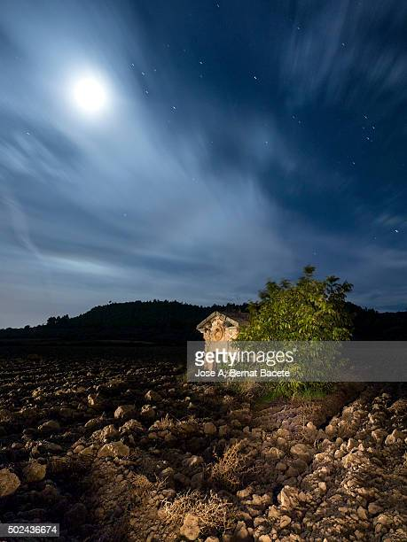 Shed of ancient stone in a field ploughed in the moonlight