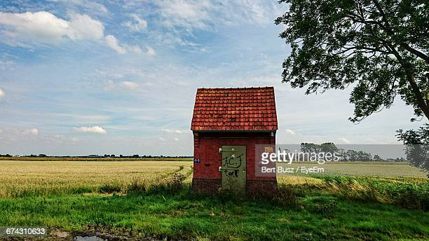 shed on grassy field against sky - groningen province stock photos and pictures