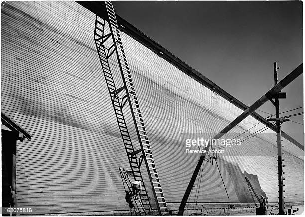 'Shed Six' short and tall ladders propped against a high brick wall USA 1943