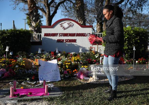 Sheena Billups prepares to lay flowers in a memorial setup at Marjory Stoneman Douglas High School for those killed during a mass shooting on...
