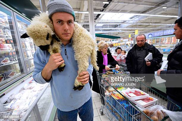 A sheep farmer holds a lamb on March 23 2013 at a supermarket in PlandeCampagne near Marseille during an action to protest against the falling lamb...