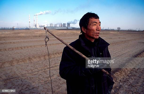 A sheep herder stands on his farm near a coal power plant in Baotou Inner Mongolia China Baotou is an excellent example of a oneindustry town and...