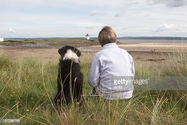 sheepdog cross at the beach with owner right - black hairy women stock pictures, royalty-free photos & images
