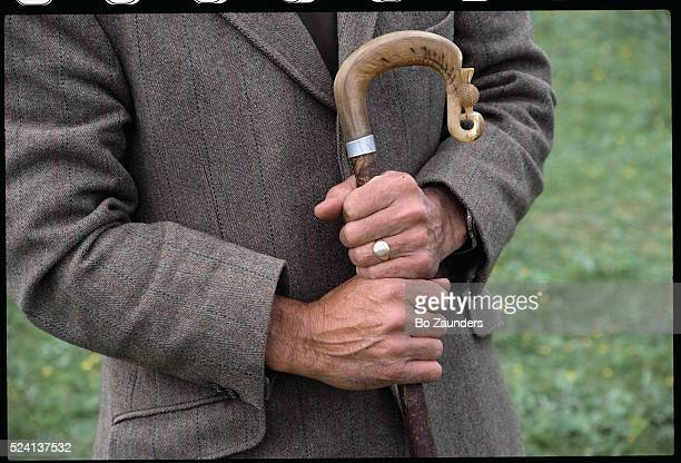 A sheepdog trial contestant holds a walking stick with a curved handle