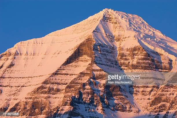 Sheer snow covered cliffs of Mount Robson 3,954 m (12,972 ft) glowing in the winter sunset, Mount Robson Provincial Park British Columbia, Canada