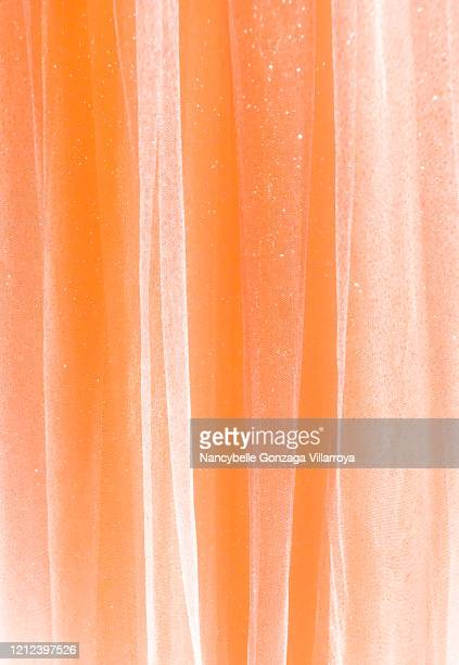 sheer tulle fabric in shimmery orange peachy colour - sheer fabric stock pictures, royalty-free photos & images