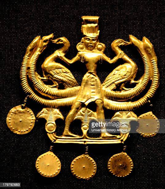 Sheet gold pendant showing a Cretan nature god The figure wears a Minoan kilt a tall headdress bracelets and earrings He stands in the attitude of...