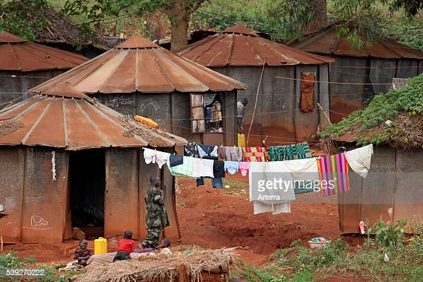 Sheet iron huts and soldier in village near Kampala Uganda Africa