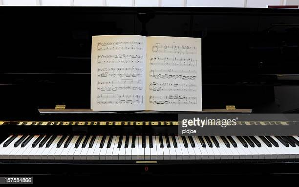 sheet music on black lacquered piano xxxl image - grand piano stock photos and pictures