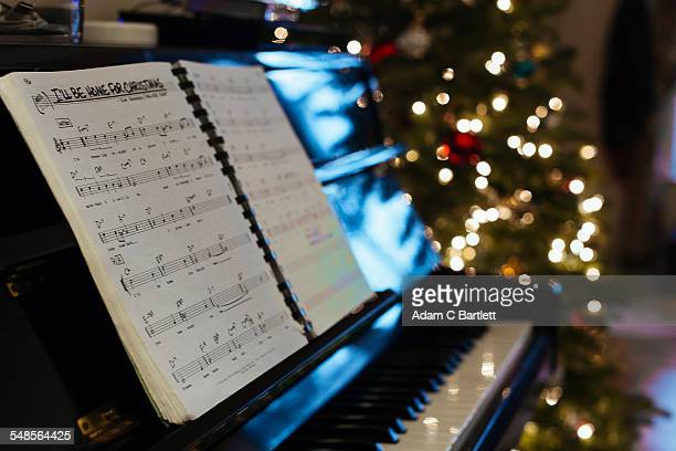 Sheet music on piano, Christmas tree in background