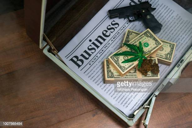a sheet of marijuana for money, dollars and cannabis, a legal and black market business - marijuana money stock photos and pictures