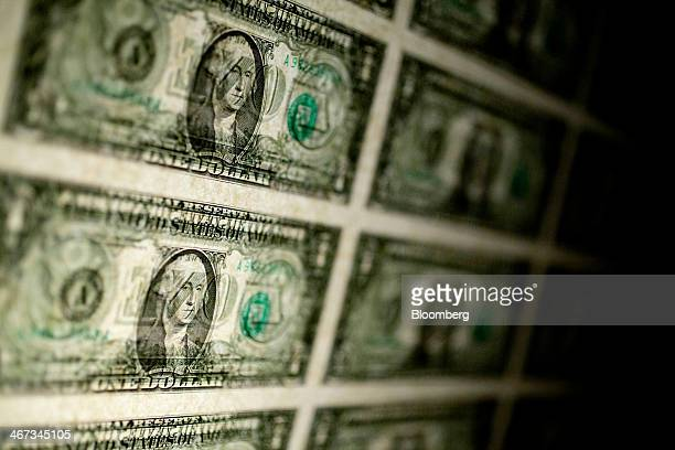 A sheet of uncut US $1 bills is arranged for a photograph in Washington DC US on Thursday Feb 6 2014 A suspension of the federal debt limit enacted...