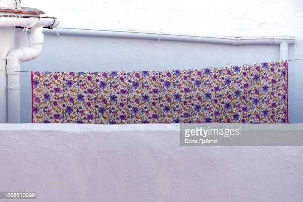 sheet or tablecloth with purple flowers drying on a clothesline between white walls - dorte fjalland fotografías e imágenes de stock