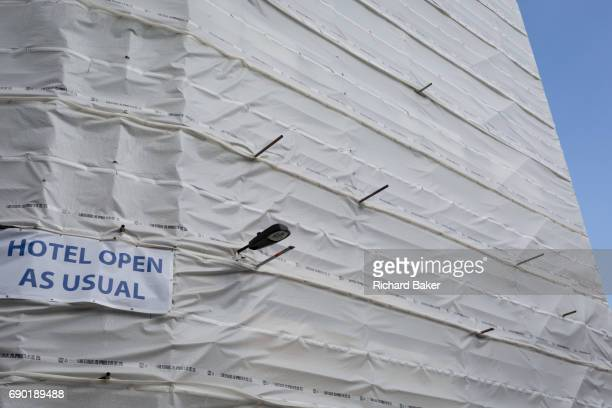 Sheeting covers the exterior of a Holiday Inn which is still managing to remain open in the borough of Southwark on 14th May 2017 in London England