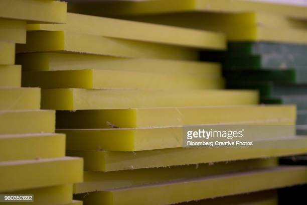 Sheets of acrylic imported from Europe are stacked on a factory floor