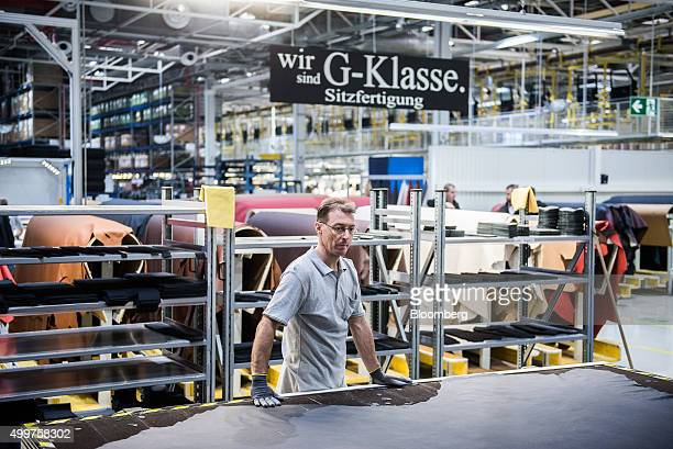 Sheets of fine quality leather sit on rails ahead of use for interior trim for MercedesBenz AG GClass automobiles on the production line at the Magna...