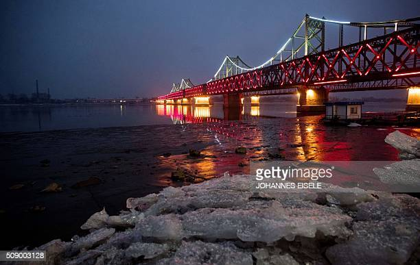 Sheets of ice are seen next to the bridge on the banks of the Yalu River at the Chinese border town of Dandong across from the North Korean town of...
