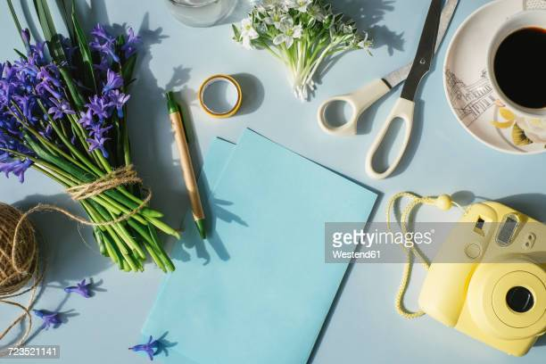 Sheets of paper, camera, scissors, cup of coffee and spring flowers on light blue background