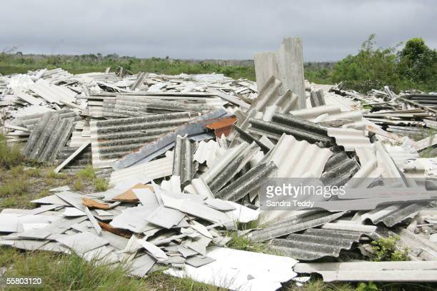 Sheets of roofing containing asbestos lay abandoned in a field October 30 2004 after being removed during and after cyclone Heta that struck Niue ten...