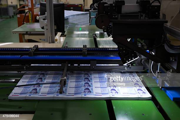 Sheets of South Korean 1000 won banknotes move through a machine on the production line at the Korea Minting Security Printing ID Card Operating Corp...