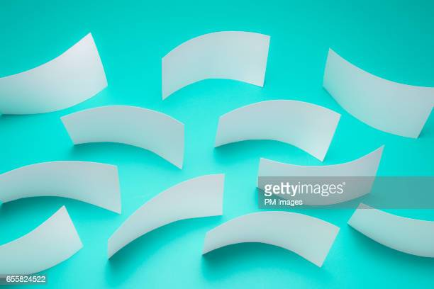 Sheets of white paper flowing over green background