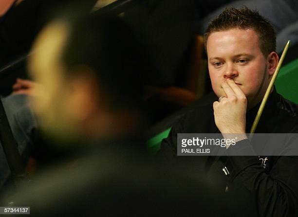 Sheffield, UNITED KINGDOM: Current world champion Shaun Murphy watches his opponent, Thailand's James Wattana, during his first round match against...