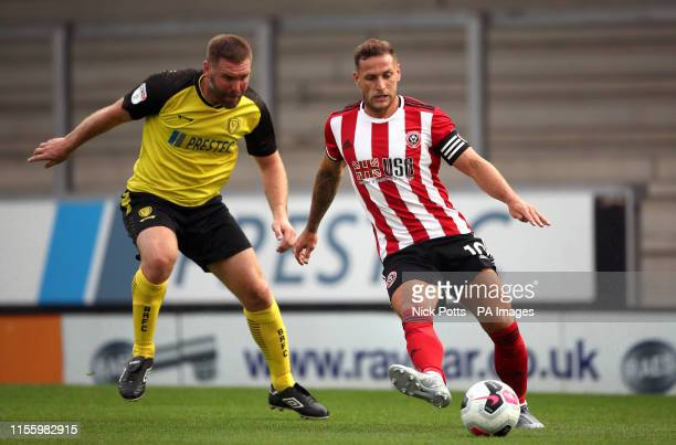 Sheffield United's Billy Sharp and Burton Albion's Jake Buxton battle for the ball during the preseason friendly match at the Pirelli Stadium Burton