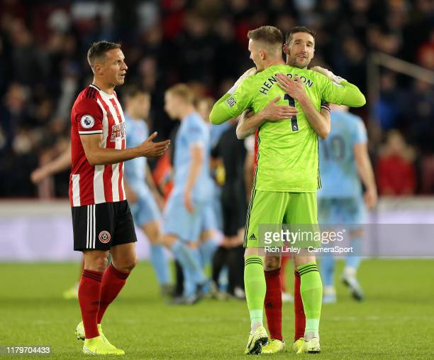 Sheffield United's Dean Henderson embraces Chris Basham as they celebrate at the final whistle during the Premier League match between Sheffield...